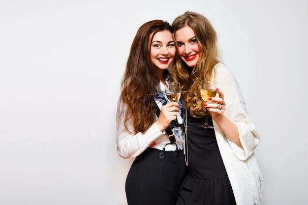 Due ragazze dei migliori amici che si divertono alla festa in bianco e nero, bevono champagne sorridendo e pettegolezzi, sorelle gioiose che celebrano la festa di compleanno, vestiti alla moda eleganti, sfondo bianco.