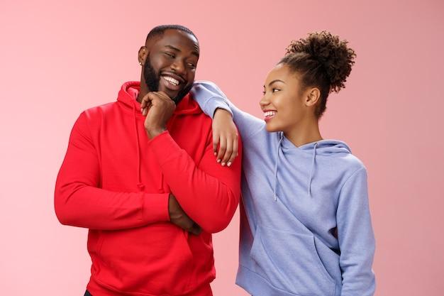 ピンクの背景のチットチャット自信を持ってリラックスしたポーズを立って、一緒に時間を過ごすように冗談を言って笑って話している彼の肩に寄りかかって女性を笑顔の男を楽しんでいる2人の親友