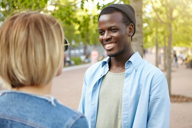 Two best friends meeting on street: dark-skinned male in trendy hat and shirt, smiling broadly while having conversation with his female friend, being glad to meet her accidentally in green park