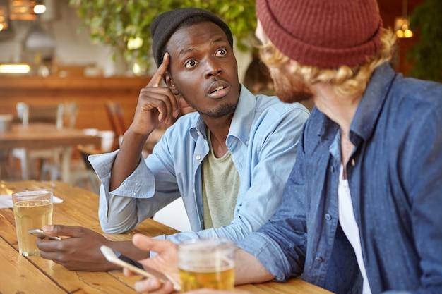 ビールを持ってパブで電子機器を使用している2人の親友または大学の仲間:認識できない白人の友人と話しているアフロアメリカンの男性がショックで完全に信じられない様子で彼を見ている