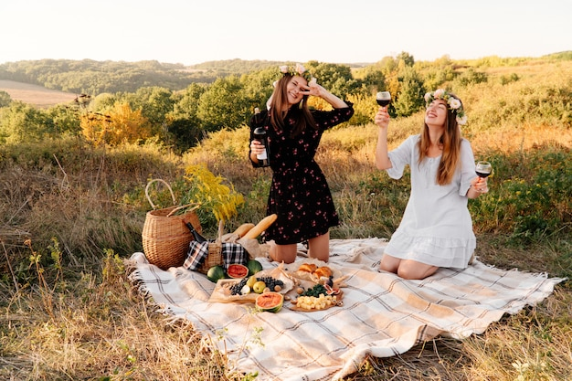 Two best friends on picnic in the field laying on the laid smiling