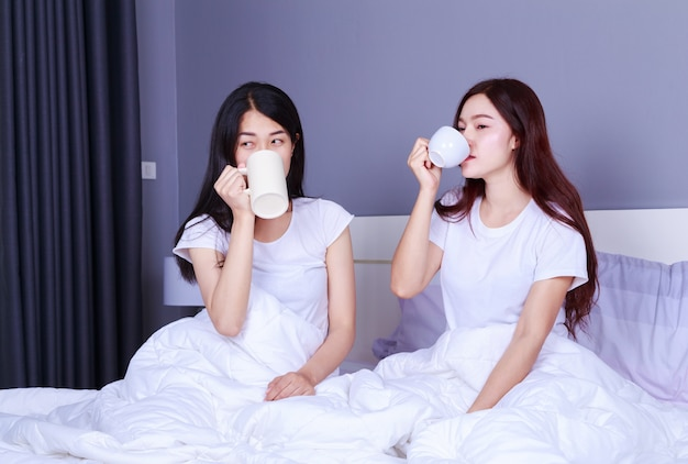 Two best friends talking and drinking a cup of coffee on bed in bedroom