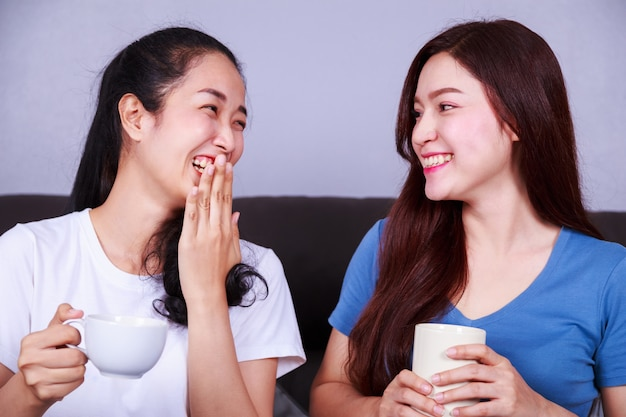 Two best friends talking and drinking a cup of coffee on sofa in living room
