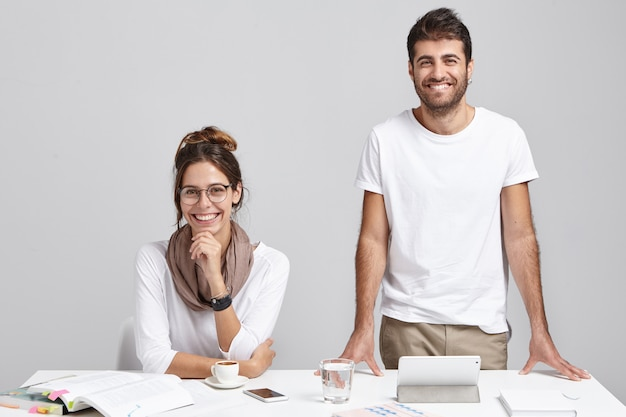 Two best friends with happy expressions work together at modern office, make future project