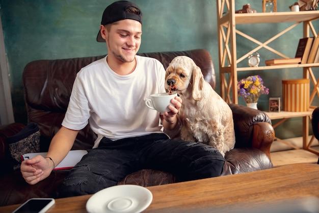 Два лучших друга молодой человек и американский кокер-спаниель кремового цвета сидят на диване у себя дома и пьют чай. понятие домашней атмосферы, дружбы, удаленного офиса, обучения из дома.