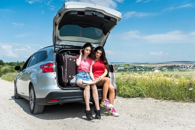 Two best girlfriends  sitting on car trunk and relaxing after trip enjoy summer time