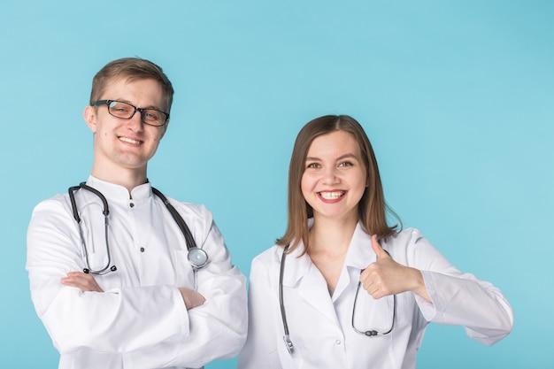 青い表面に立って親指を示す白いコートを着た2人の最高の賢いプロの笑顔の医者の労働者。