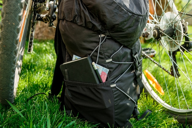 Two bicycle wheels and black backpack tourist equipment with green outside background, back view.