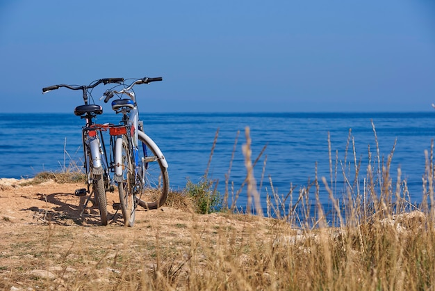 Two bicycles on the beach on  background a blue sea on a sunny day.