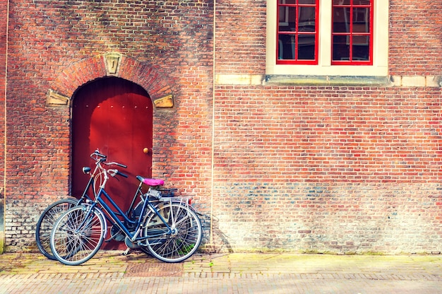 Two bicycles near the red brick wall. amsterdam, netherlands