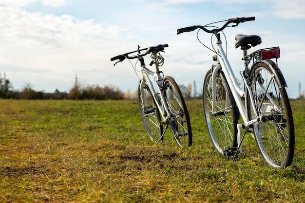 山々が野外をサイクリングしている未舗装の道路の畑に2台の自転車が立っています