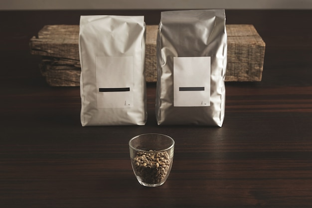 Two big hermetic packages with blank labels near transparent glass with raw sampled coffee beans