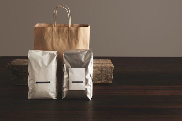 Two big hermetic packages with blank labels presented in front of craft paper bag and rustic wooden brick on red table
