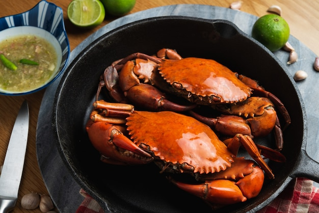 Two big mud crab in a cast iron pan with spicy chilli sauce on table.