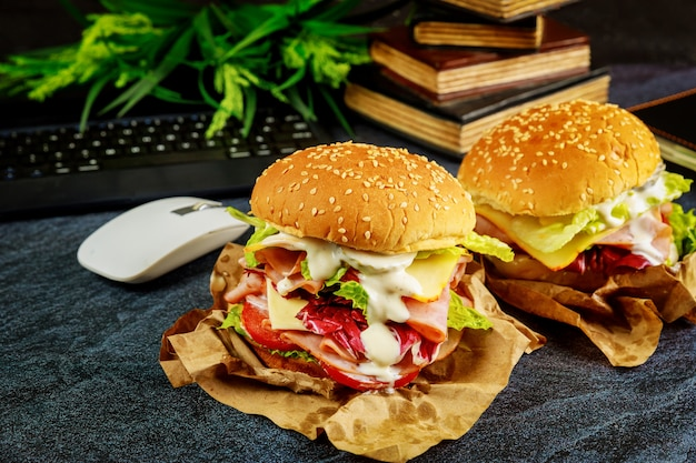 Two big sandwiches on dark desk with keyboard, mouse and books