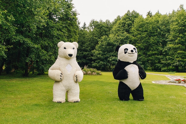 Two big teddy bears in the park in the summer