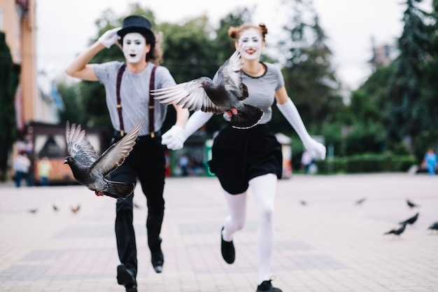 Two birds flying in front of running mime couple on pavement
