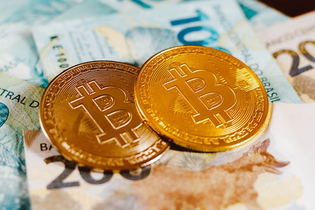 Two bitcoin coins on top of one hundred brazilian reais bills