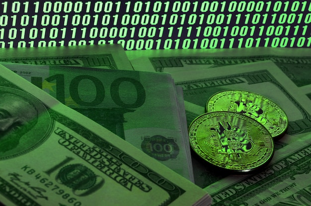 Two bitcoins lies on a pile of dollar bills on the background of a monitor depicting a binary code