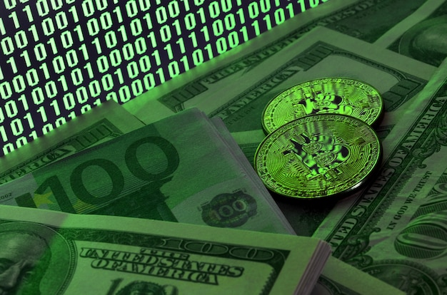 Two bitcoins lies on a pile of dollar bills on the background of a monitor