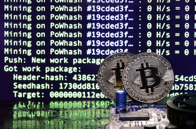 Two bitcoins lies on a video card surface with background of screen display