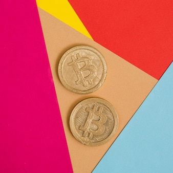 Two bitcoins on many colorful background