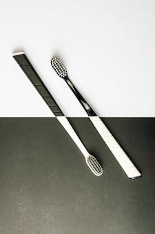 Две черно-белые зубные щетки на монохромном.