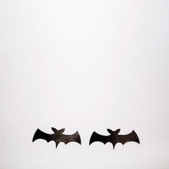 Two black bats on white