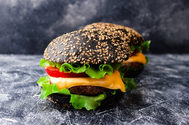 暗いテーブルにゴマの黒いパン、牛肉のカツレツ、チーズ、野菜を添えた2つの黒いハンバーガー。閉じる。選択的なソフトフォーカス。テキストコピースペース