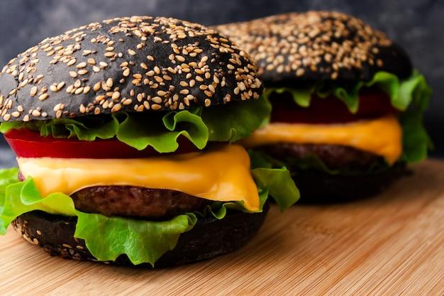 木製の素朴なまな板のテーブルにゴマの黒いパン、牛肉のカツレツ、チーズ、野菜を添えた2つの黒いハンバーガー。閉じる。選択的なソフトフォーカス。テキストコピースペース