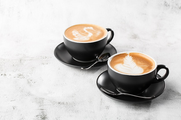 Two black cups of hot latte coffee with beautiful milk foam latte art texture