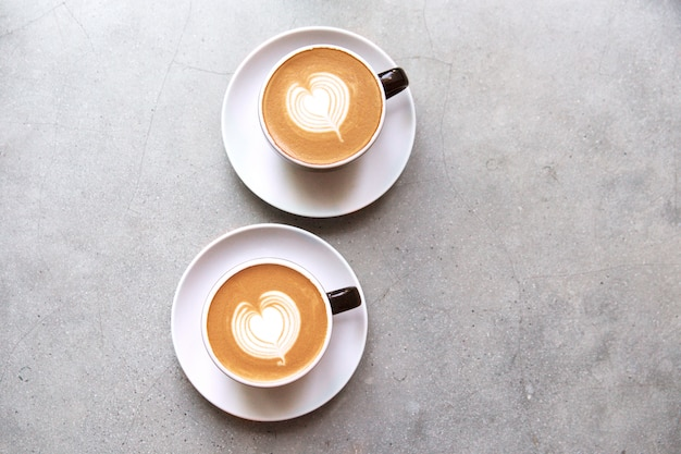 Two black cups of tasty cappucino with love art latte.