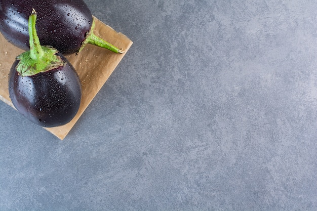 Два черных баклажана с каплей воды на каменном фоне.
