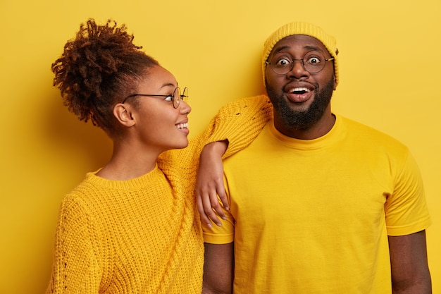 Two black friends in yellow clothes, have joyful looks, african american woman leans on shoulder of bearded guy