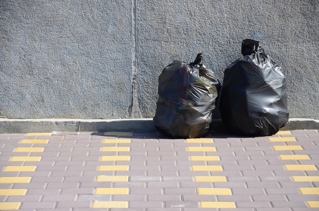 Two black garbage bags on tiled street floor at concrete fence in city