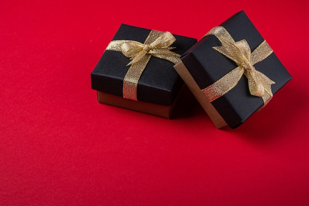 Two black gift box with golden ribbons on red paper