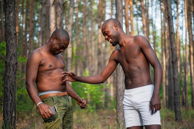 Two black guys having fun and joking while standing shirtless