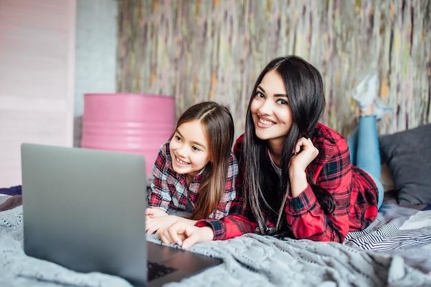 一緒に勉強しているラップトップを使用して10代と就学前の年齢の2人の黒髪の姉妹