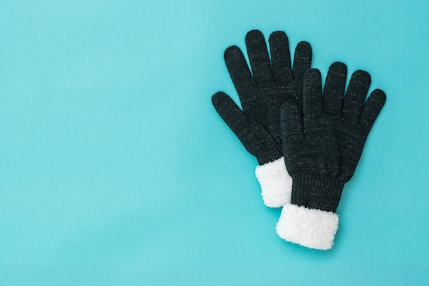 Two black knitted women's gloves lying on top of each other on a blue background. the concept of hope and meeting. fashion women's accessories.