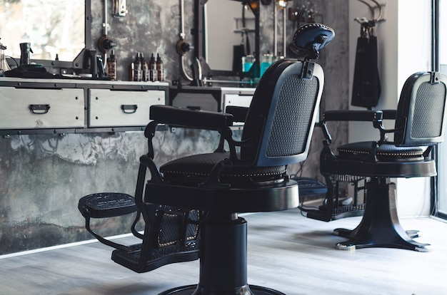 古いスタイルの理髪店にある 2 つの黒い革と鉄の理髪椅子
