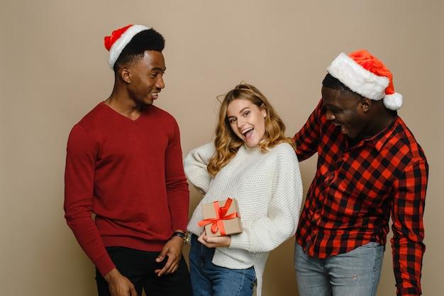 2人の黒人男性と白人女性がベージュの背景でクリスマスと新年を祝い、贈り物を見てください。明るい贈り物でホリデーパーティーの準備ができている親友の屋内の肖像画。