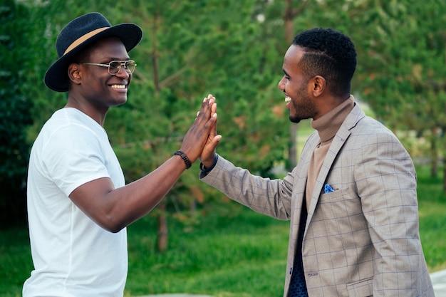 세련된 양복을 입은 두 흑인 남성이 여름 공원에서 만났습니다. 아프리카계 미국인 친구 히스패닉 사업가는 야외에서 서로 인사하는 하이파이브를 포용합니다. 성공적인 거래 개념