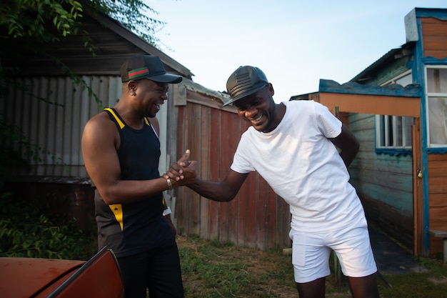 Two black men laughing and shaking hands in the background of village house
