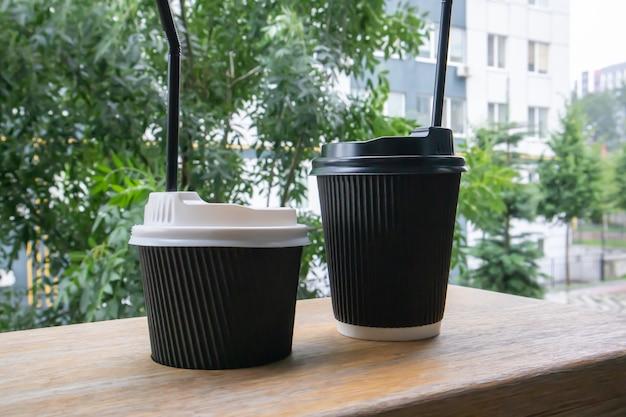 카페, 커피숍 또는 레스토랑의 나무 테이블에 화창한 날씨에 야외에서 뚜껑이 있는 검은색 종이 커피 컵 2개.