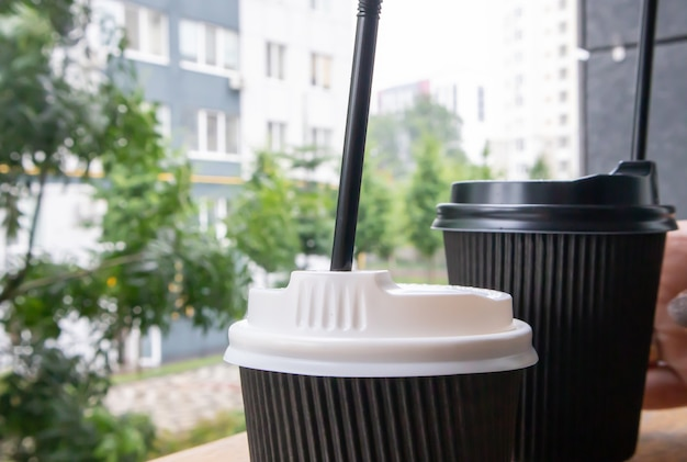 Two black paper coffee cups with lids outdoors in summer in sunny weather on a wooden table of a cafe, coffee shop or restaurant.