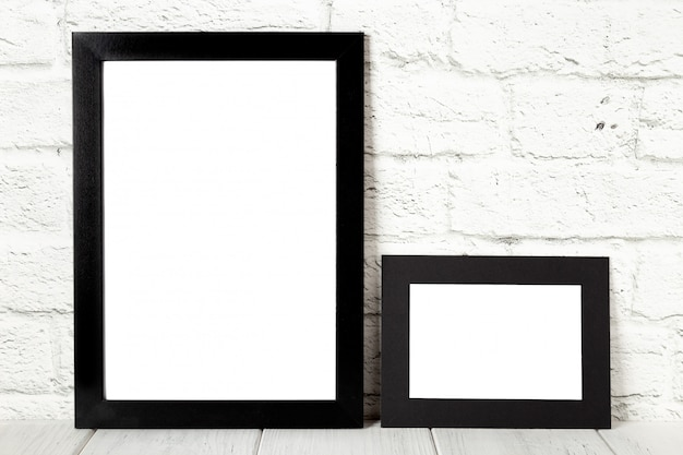 Two black photo frames on wooden table. mockup with copy space