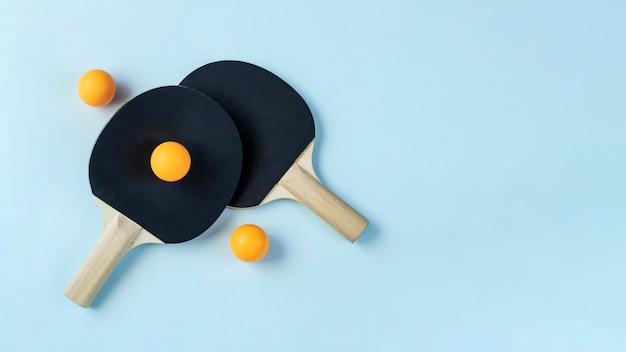 연한 파란색 배경에 검은색 탁구 패 2개와 노란색 공 3개