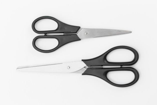 Two black scissors on white surface