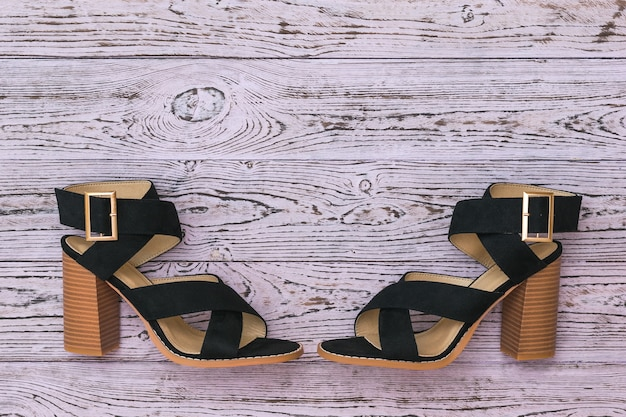 Two black summer womens shoes opposite each other on a wooden background