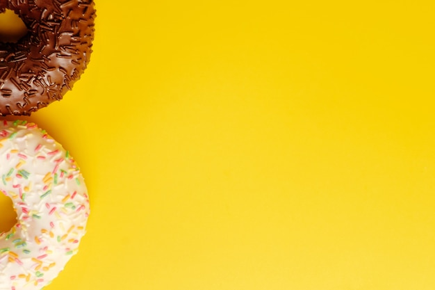 Two black and white donuts on yellow background top view copy space
